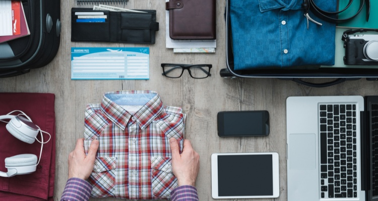 what to pack in your carry-on: Getting ready for a trip and packing a suitcase, a man is holding his shirt before putting it into his bag