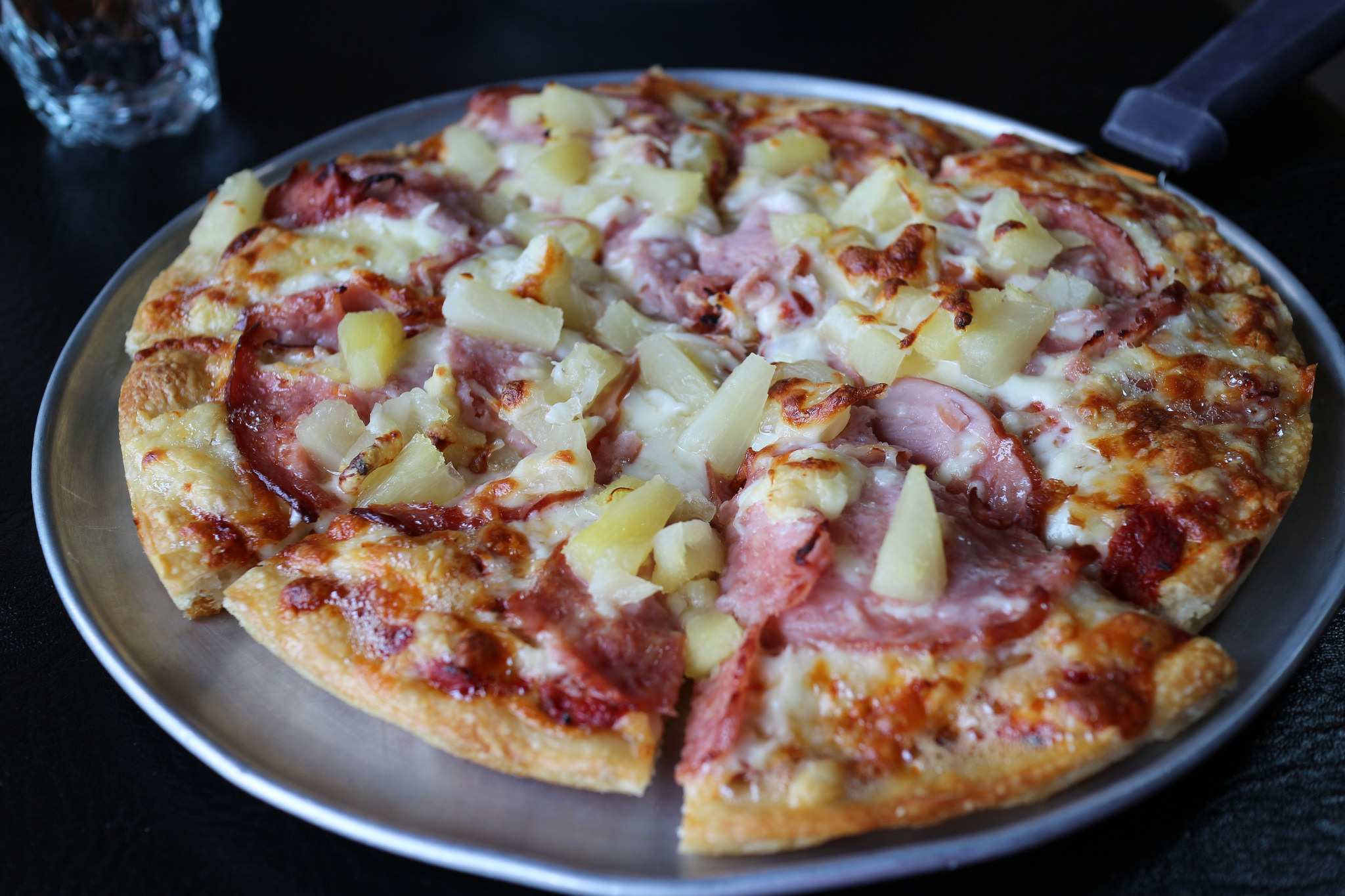 """Athena Pizza - Hawaiian Pizza"" by Elsie Hui is licensed under CC 2.0."