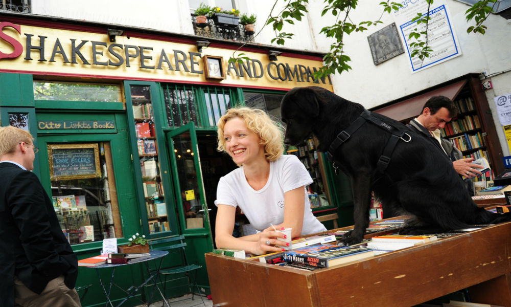 woman with a black dog outside of Shakespeare and company bookstore in Paris