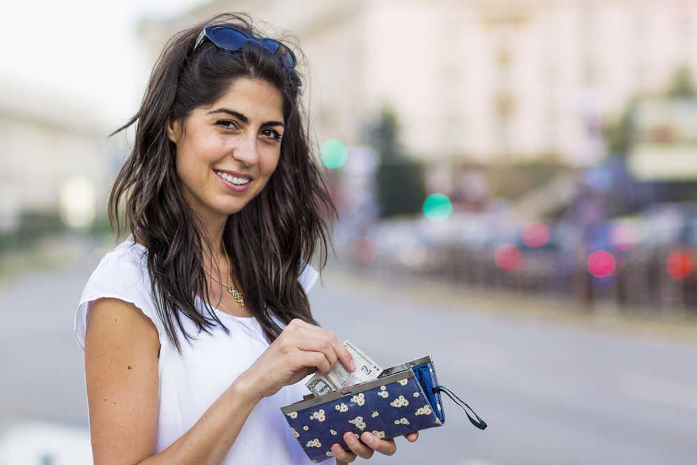 woman smiling and holiding a wallet