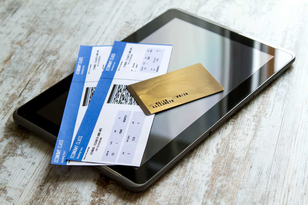 a tablet with two airline tickets with credit card