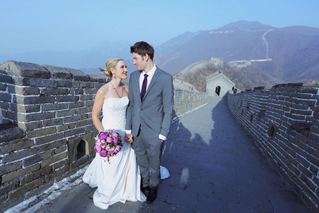 PIC FROM FORTITUDE PRESS (PICTURED - AMELIA AND BRETT GETTING MARRIED AT THE GREAT WALL OF CHINA) A LOVED-UP couple whose wedding plans were dashed after they clashed with a family member's marriage have gone on to tie the knot in EIGHT different countries. Amelia Irwin, 32, was faced with a dilemma after her wedding was planned in the same month as that of a family member of her partner Brett, 33, last year. But the couple, who met nine years ago, decided to tie the knot in a registry office so they could save £10,000 which they went on to use to travel the globe. And since they got married in Trowbridge last year, the couple have been blessed and enjoyed ceremonies at locations across the globe including Paris, Moscow, Beijing and Nepal. SEE FORTITUDE PRESS COPY