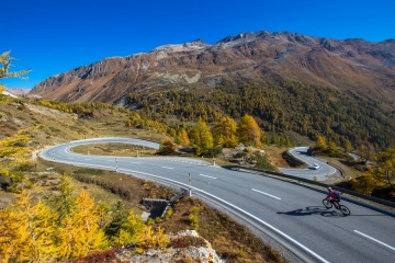 Mountain road in Switzerland. Bernina mountain pass street on a beautiful autumn day. Road through the alps in Europe. Fantastic sunny day for a road trip with a car. Cyclist on a curved road.