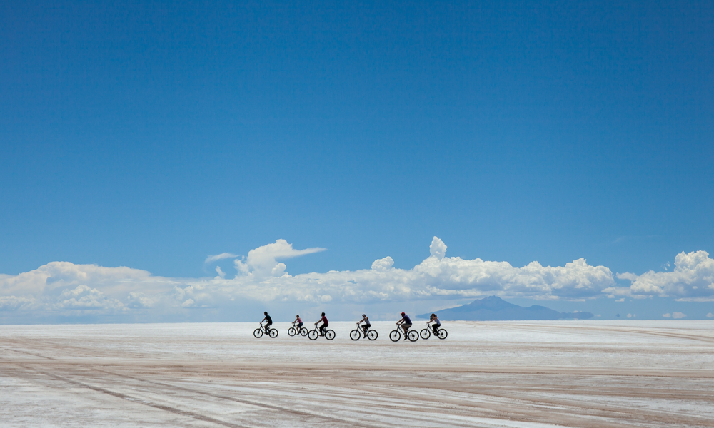 cyclists group riding the desert of salt, in salares de Uyuni, Bolivia.
