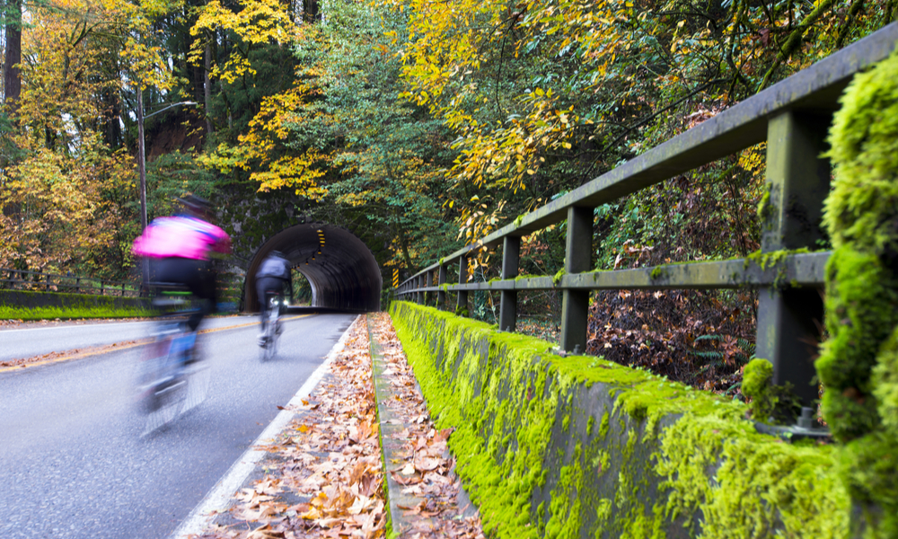 Cyclists rapidly moving toward an arched tunnel, carved into the rock,