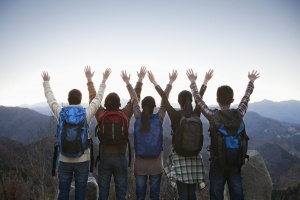 group of hikers with their hands in the air