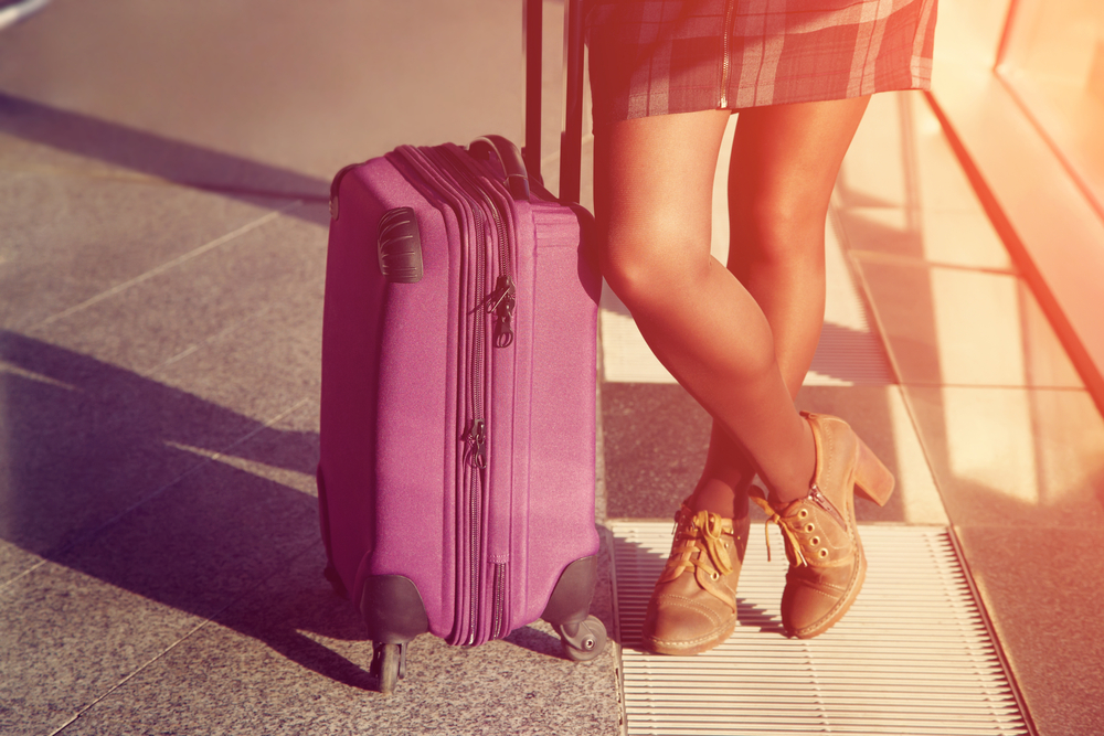 female legs closeup. stylish woman with a suitcase standing at the window at the airport. traveler waiting airplane flight