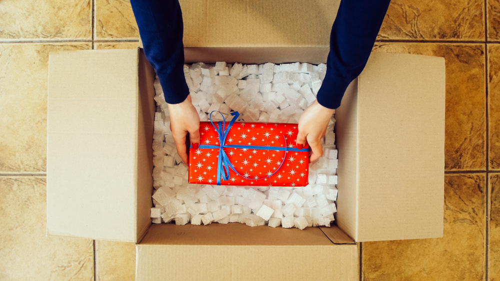 Woman hands opening a parcel contains a gift. Unpacking box with another box. Surprise. Red present box. People, delivery, shipping service, opening cardboard box or parcel at home.