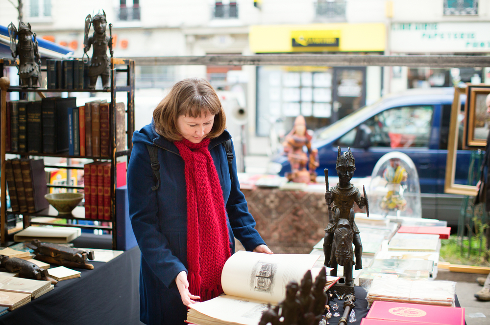 Girl selecting a book on a Parisian flea market