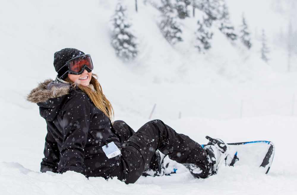 young american girl snowboarding in Idaho with snowfall