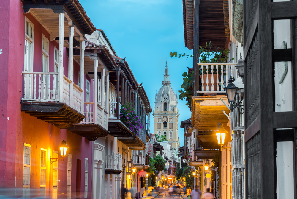 Street view of Cartagena, Colombia after sunset with cathedral visible in the background