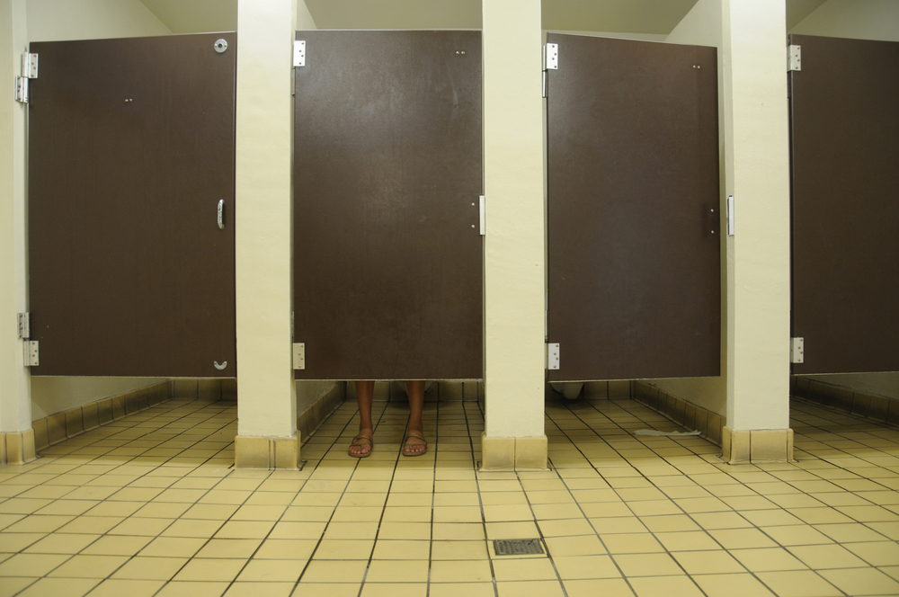 Feet showing under bathroom door, in public restroom with four stalls