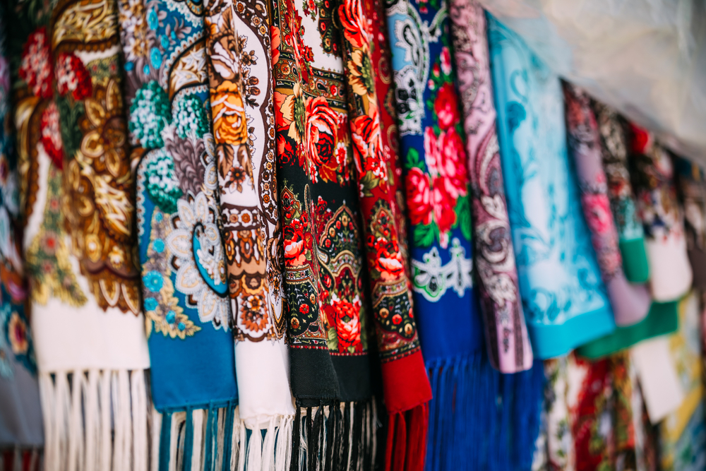 Rows of traditional Russian colorfull scarfs and headscarfs in market. Popular souvenir from Russia