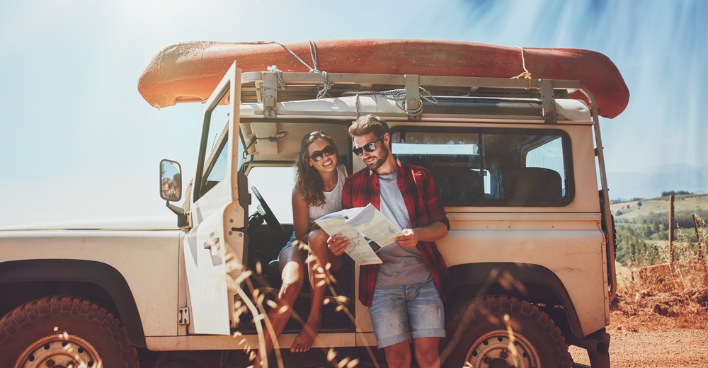 Young couple taking a break to look at a map while on a roadtrip. Young man and woman on country road looking for directions on map.