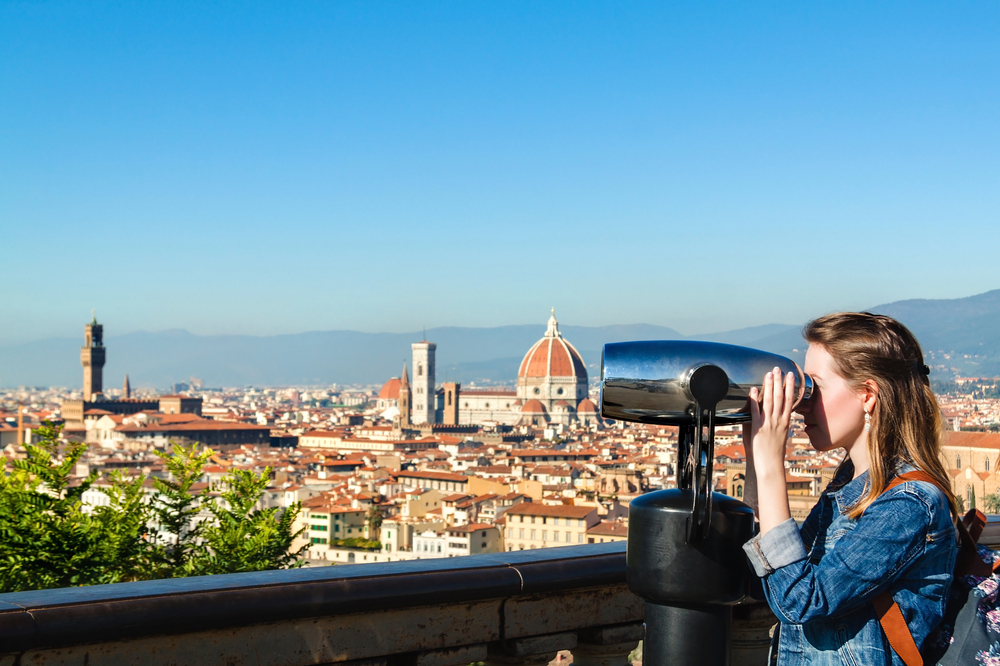 Young girl looking through a coin operated binoculars and enjoying the view of Florence, Tuscany, Italy.
