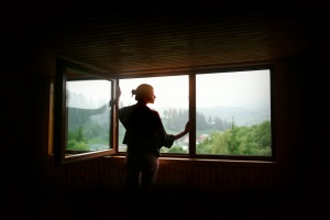 silhouette of woman in sunshine at big wooden window with view on sunset in mountains, tranquil moment or relax concept, space for text