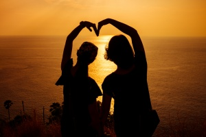 Silhouette photo of two girls arranged their arms in heart shape with sunset background