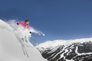 Expert female skier making jump off side of mountain.