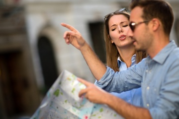 Lost couple discussing which way to go and holding a map