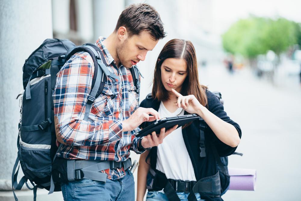 Couple of backpackers looking at city map on tablet computer
