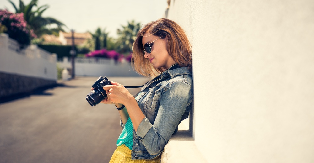 Portrait of a young, fit and attractive woman taking a photo outdoor. Posing on the street on a sunny summer day. Girl looking at the camera.