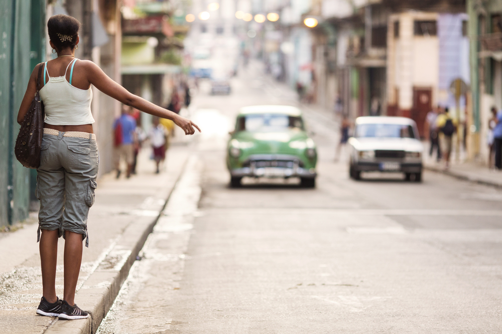 Young professional woman hitching a taxi in Havana, Cuba