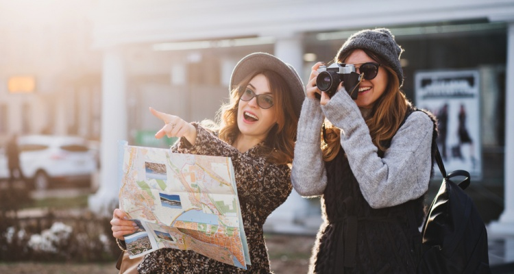 Happy travel together of two fashionable girls in sunny city centre. Young joyful women expressing positivity, using map, vacation with bags, camera, making photo, cheerful emotions, great mood