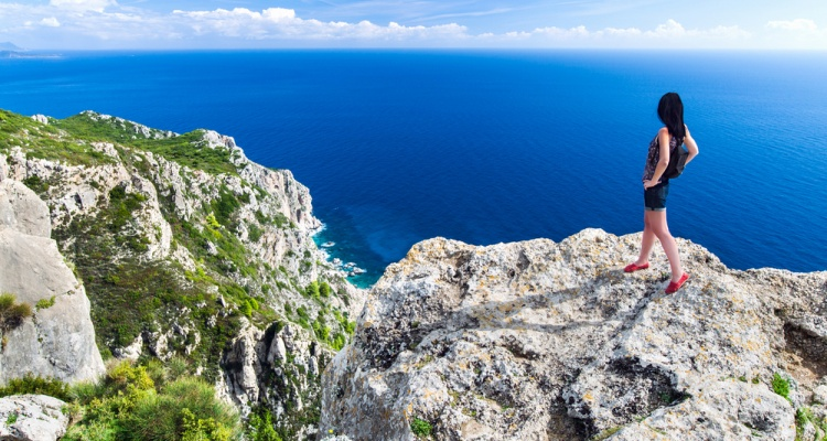 Travel girl stands on the edge of a high cliff above sea. Back view young female. Greece islands landscape. Travel Concept.