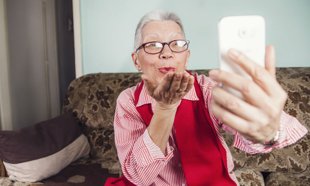 elderly woman taking a video call on phone
