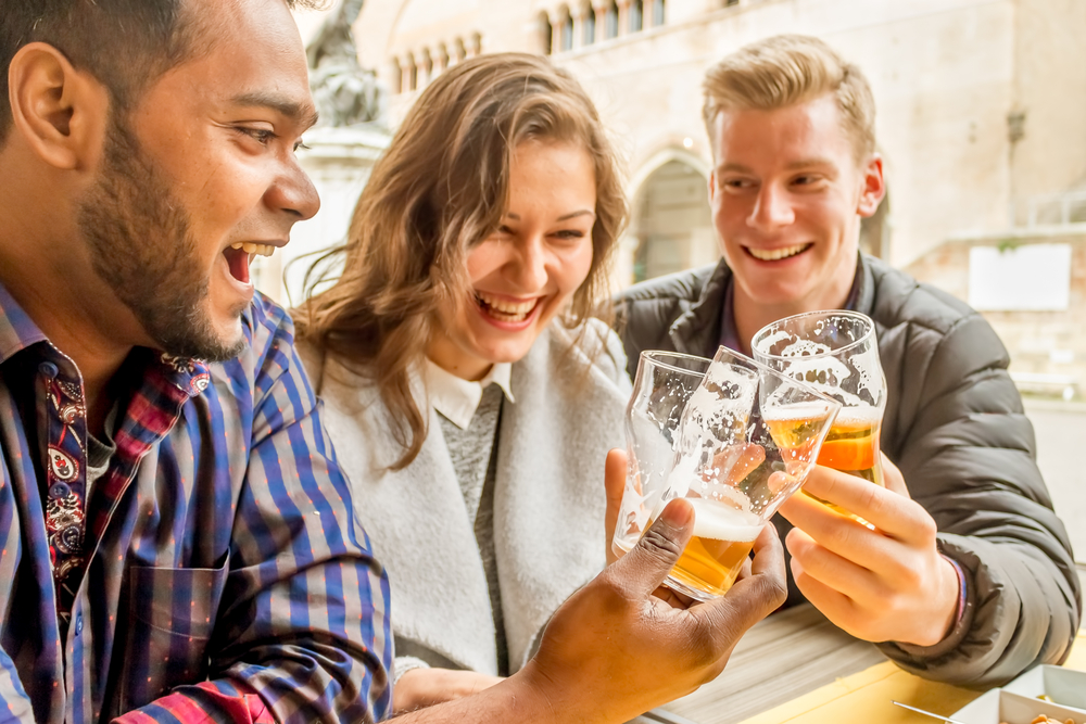 cheerful multi-ethnic friends of drinking beer and say cheers - multi-racial best friends having fun and laughing in a bar - focus on glasses, custom color tones and flare to give spontaneous look