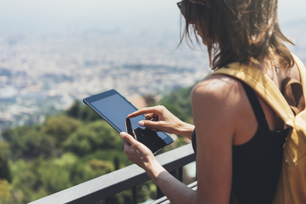 Girl with bright backpack planning travel plan. Traveler on background panoramic view of the city, binoculars. Mock up for text message. Barcelona Tibidabo. Female hands using tablet, holding gadget