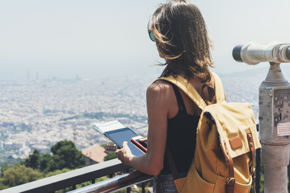 Girl with bright backpack planning travel plan. Tourist traveler on background panoramic view of city, coin operated binoculars. Mock up. Barcelona Tibidabo. Female hands using tablet, holding gadget