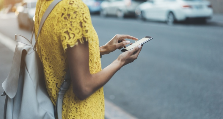 Young hipster girl in yellow dress traveling in Europe and using an app for search local cafe or sightseeing, female hands typing on touch screen of cellphone device to send an sms message