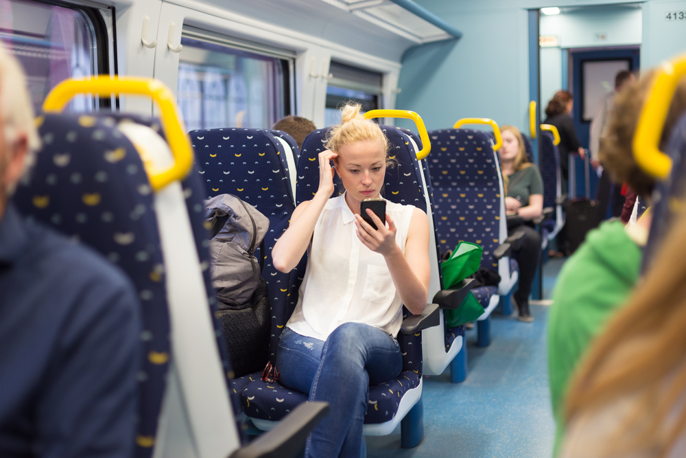 Woman workin on smart phone while traveling by train. Business travel concept.