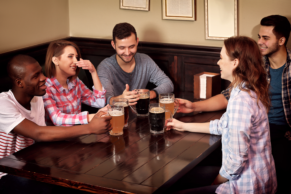 Happy friends drinking beer in pub
