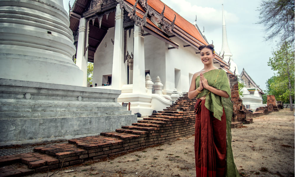 thai girl greeting people with temple in background