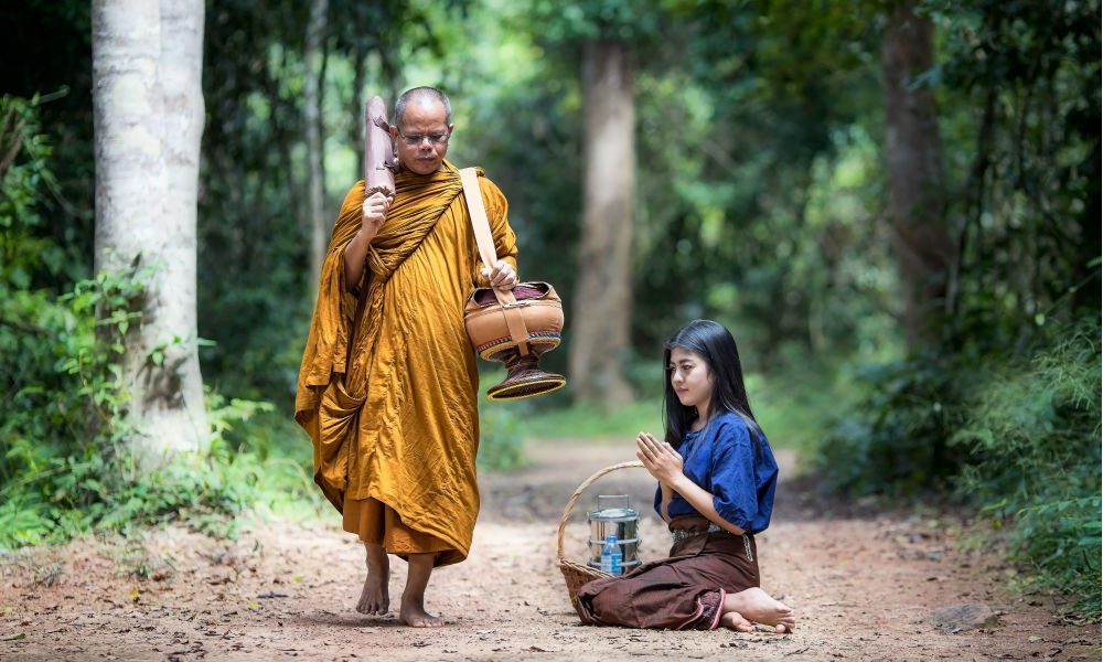 young thai girl bows to a monk