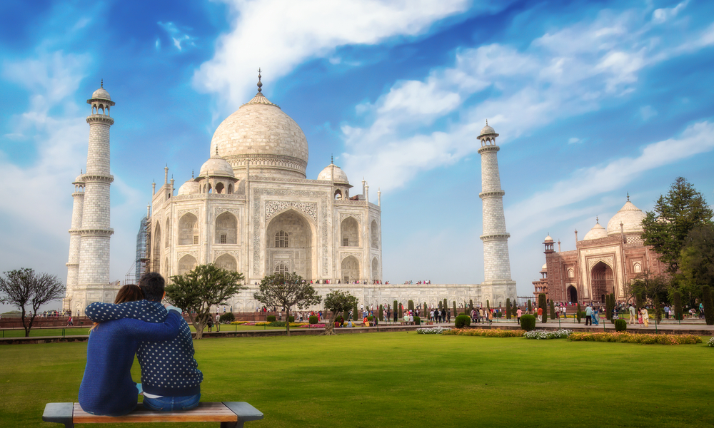 Romantic couple enjoy the view of the Taj Mahal at Agra, India.
