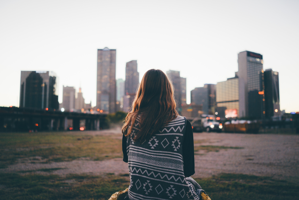A traveler girl is looking at Dallas skyline during in the evening.