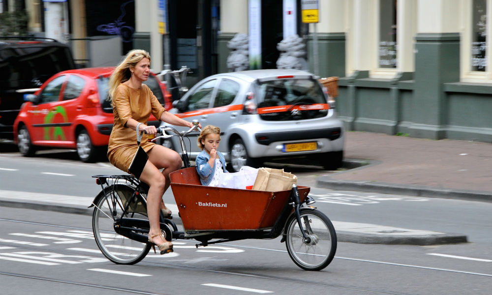 woman riding a bakfiet in amsterdam