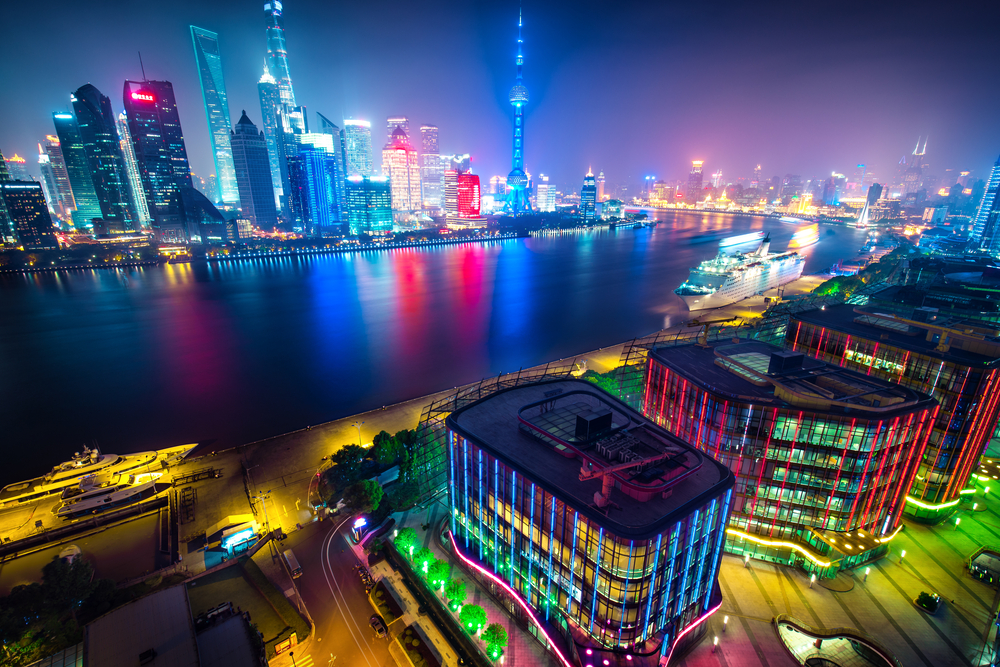 Aerial panoramic view over a big modern city by night. Shanghai, China. Nighttime skyline with illuminated skyscrapers