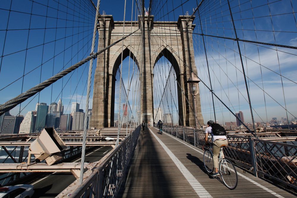 Bicyclist heading to Manhattan on the Brooklyn Bridge in morning light with blue sky and wispy clouds.