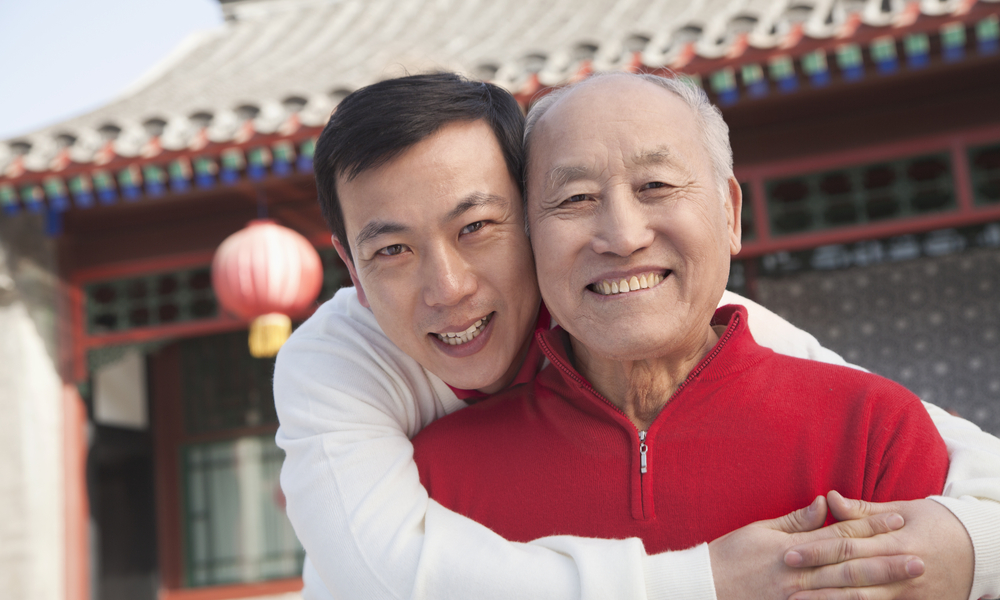 Adult son with senior father visiting homeland
