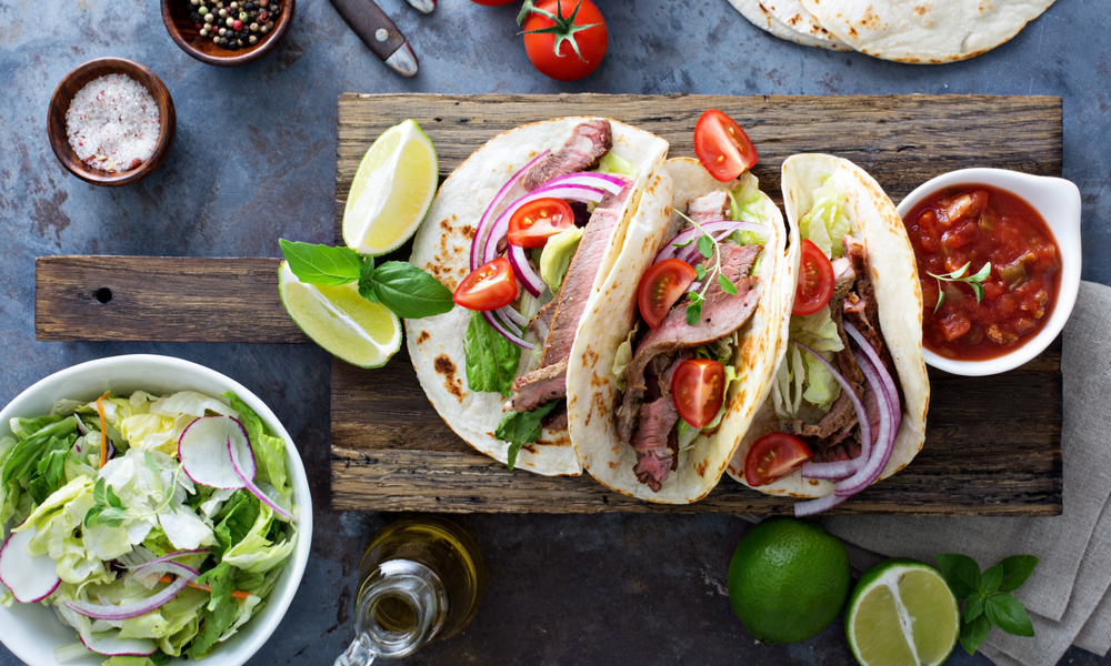 Steak tacos with sliced meet, salad and tomato salsa on a cutting board