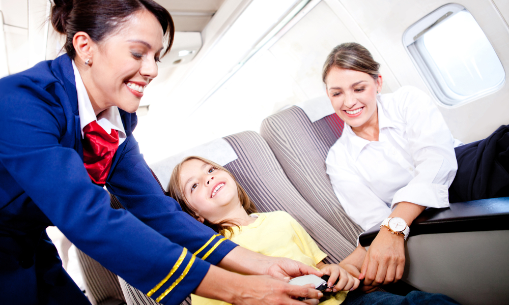 Flight attendant fastening seat belt to boy for a safe trip