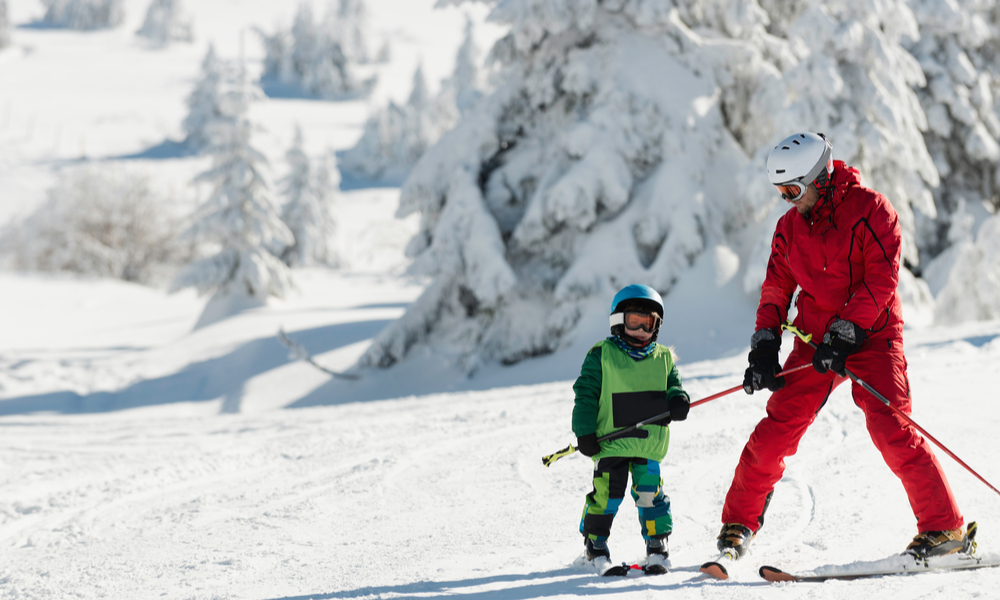 Little boy learning to ski with instructor