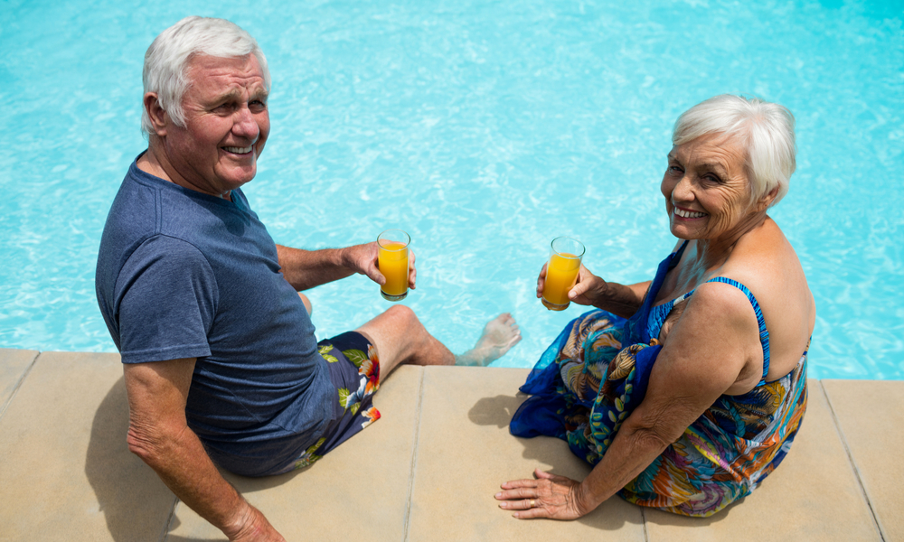 Portrait of senior couple holding juice glasses near poolside