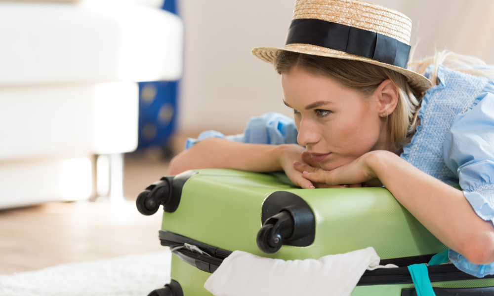 woman laying across suitcase