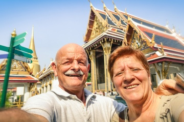 Senior happy couple taking a selfie at Grand Palace temples in Bangkok - Thailand