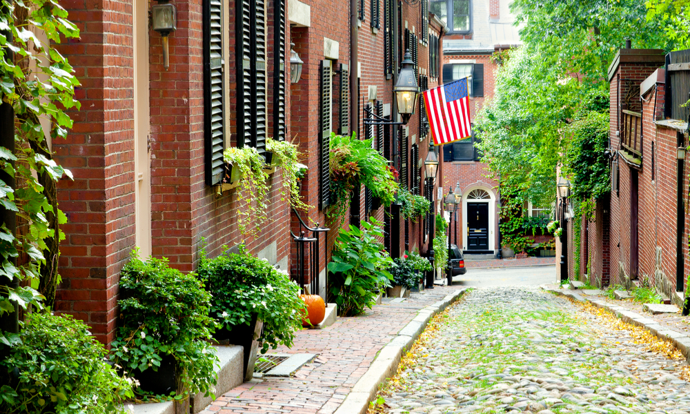 Cobblestone street in Boston. Historic Acorn Street in Beacon Hill, called the most picturesque street in America, with a row of vintage red brick buildings.